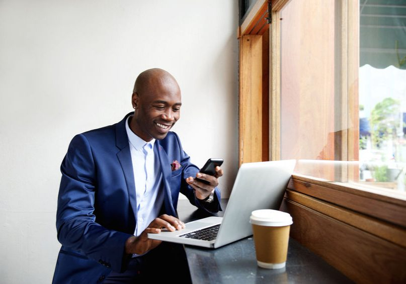 51498038 - portrait of happy african businessman using phone while working on laptop in a restaurant